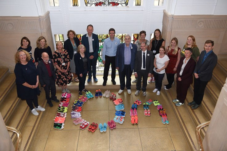 Andy Burnham with people in front of running shoes spelling out '10 m'